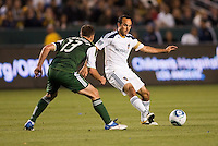 Landon Donovan (10) attempts to navigates around Jack Jewsbury (13) of the Portland Timbers. The LA Galaxy defeated the Portland Timbers 3-0 at Home Depot Center stadium in Carson, California on  April  23, 2011....