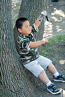 Hmong boy age 8 with camo shirt plays with bow and arrow. Hmong Sports Festival McMurray Field St Paul Minnesota USA