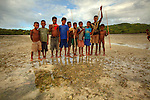 Children at Hessessai Bay at PanaTinai (Panatinane)island in the Louisiade Archipelago in Milne Bay Province, Papua New Guinea.  The island has an area of 78 km2..The Louisiade Archipelago is a string of ten larger volcanic islands frequently fringed by coral reefs, and 90 smaller coral islands located 200 km southeast of New Guinea, stretching over more than 160 km and spread over an ocean area of 26,000 km? between the Solomon Sea to the north and the Coral Sea to the south. The aggregate land area of the islands is about 1,790 km? (690 square miles), with Vanatinai (formerly Sudest or Tagula as named by European claimants on Western maps) being the largest..Sideia Island and Basilaki Island lie closest to New Guinea, while Misima, Vanatinai, and Rossel islands lie further east..The archipelago is divided into the Local Level Government (LLG) areas Louisiade Rural (western part, with Misima), and Yaleyamba (western part, with Rossell and Tagula islands. The LLG areas are part of Samarai-Murua District district of Milne Bay. The seat of the Louisiade Rural LLG is Bwagaoia on Misima Island, the population center of the archipelago.PanaTinai (Panatinane) is an island in the Louisiade Archipelago in Milne Bay Province, Papua New Guinea. The island has an area of 78 km2..The Louisiade Archipelago is a string of ten larger volcanic islands frequently fringed by coral reefs, and 90 smaller coral islands located 200 km southeast of New Guinea, stretching over more than 160 km and spread over an ocean area of 26,000 km? between the Solomon Sea to the north and the Coral Sea to the south. The aggregate land area of the islands is about 1,790 km? (690 square miles), with Vanatinai (formerly Sudest or Tagula as named by European claimants on Western maps) being the largest..Sideia Island and Basilaki Island lie closest to New Guinea, while Misima, Vanatinai, and Rossel islands lie further east..The archipelago is divided into the Local Level Government (LLG) areas Louisiade R