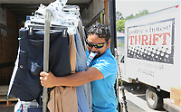 NWA Democrat-Gazette/DAVID GOTTSCHALK Kamal Kumar holds an ice cream bar Monday, July 8, 2019, in his teeth as he moves a rack of clothing into Potter's House Thrift Store in Fayetteville. The non profit reduces and discounts the prices of items based on the length of time they are in inventory. Funds raised go to the ministry of Potter's House.