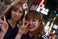 Two female soccer fans celebrate the Japan National Team qualifying for the next round of the 2018 World Cup in Russia. Japan lost to Poland  0-1 but managed to move to the next stage on points. Thousands of younger fans gathered at Tokyo's iconic Shibuya crossing to enjoy the moment with police controlling the crowds