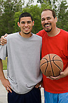 Hispanic father with his son on basketball court