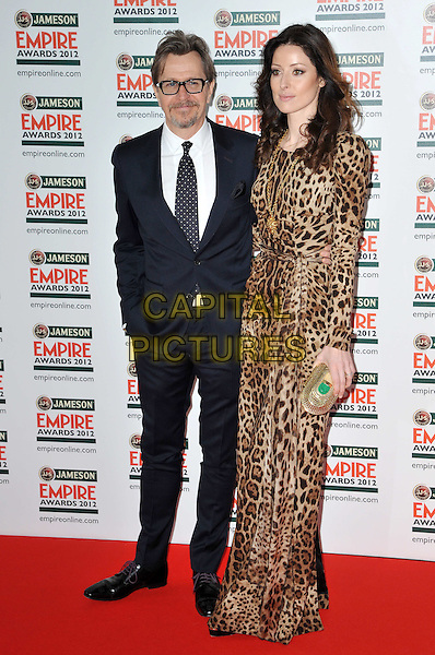 Gary Oldman & Alexandra Edenborough.The Jameson Empire Film Awards 2012, Grosvenor House Hotel, Park Lane, London, England..March 25th, 2012.full length suit brown dress leopard print married husband wife black white tie glasses goatee facial hair .CAP/BF.©Bob Fidgeon/Capital Pictures.
