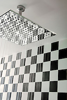 One of the large square shower heads seen in action in a bathroom of the hotel