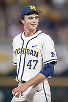 Michigan Wolverines pitcher Tommy Henry (47) smiles towards Vanderbilt Commodores baserunner Stephen Scott after he was knocked over at first base during the ninth inning of Game 1 of the NCAA College World Series Finals on June 24, 2019 at TD Ameritrade Park in Omaha, Nebraska. Michigan defeated Vanderbilt 7-4. (Andrew Woolley/Four Seam Images)