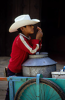 Mexican boy with hat selling icecream from his cart. Helados vendor.