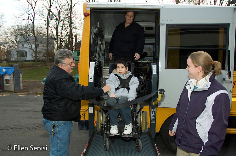 MR / Albany, NY.Langan School at Center for Disability Services .Ungraded private school which serves individuals with multiple disabilities.Child boards schoolbus using wheelchair lift operated by bus driver while his teacher watches. Boy: 8, cerebral palsy, spastic quadriplegic, nonverbal with expressive and receptive language delays.MR: AH-cfds, Hac2.© Ellen B. Senisi