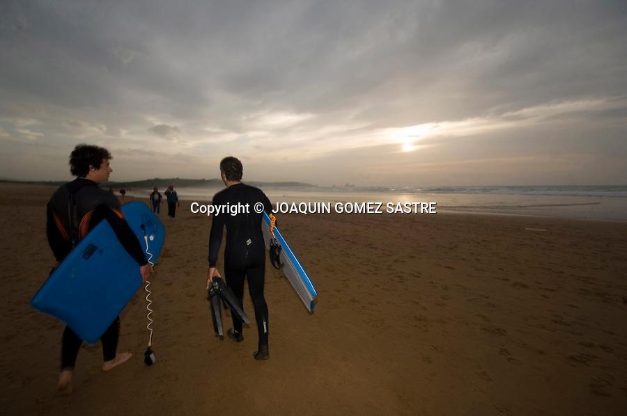 .Dos surfistas se retiran al atardecer despues de coger olas en la playa de Liencres..FOTO JOAQUIN GOMEZ SASTRE©