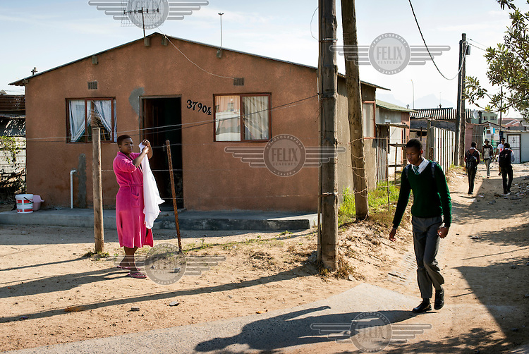 A schoolboy heads home for lunch, passing a brick built house belonging to one of Khayelitsha's more wealthy residents.