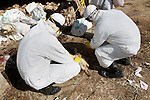 "Palestinian workers, wearing protective gear, kill a turkey at a live-poultry farm in the West Bank village of Serees, southern Jinin January 21, 2015. A flock of 17,000 turkeys has been diagnosed with the H5N1 ""bird flu"" virus in Jinin. The veterinary department of the Palestinian Authority Agriculture Ministry said it had managed to prevent an epidemic. Photo by Nedal Eshtayah"