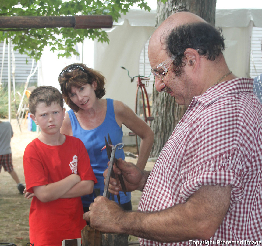 Theo Porter and his mother Susan Porter watch the blacksmith Dean Rantz during the Braintree Historical Society's annual Heritage Day, at the Thayer House and Museum on Sunday September 21 2014.(Photo by Gary Wilcox)