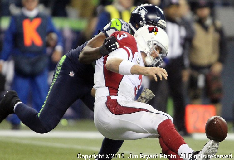 Seattle Seahawks defensive end Cliff Avril (56) forces a fumble by Arizona Cardinals quarterback Carson Palmer (3) at CenturyLink Field in Seattle, Washington on November 15, 2015. The Cardinals beat the Seahawks 39-32.   ©2015. Jim Bryant photo. All Rights Reserved.