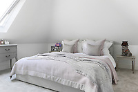 A ceramic bulldog bedside lamp looks over a double bed draped with pale pink and grey bedding in a spacious attic room