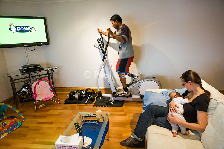 A young mother breastfeeds her baby in her living room while her husband works out on his excercise machine while watching television.<br /> <br /> 15/05/2012<br /> Hampshire, England, UK