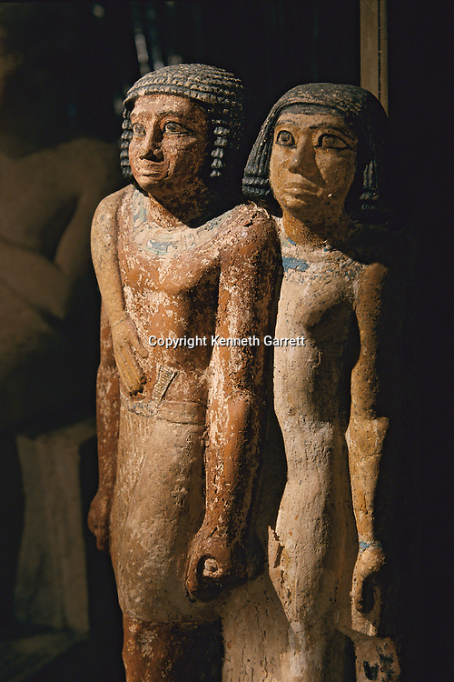 A painted limestone pair statue of a husband and wife, Old Kingdom