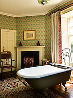 The bathroom is furnished with a free-standing bath tub