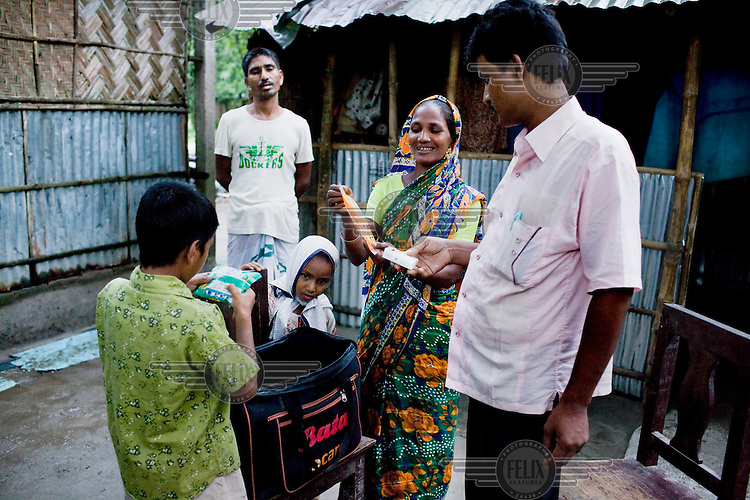 Shahida Begum, 35, meets her Hub Manager, Akhterruzzaman, in the compound of her hut in Palashbari Villlage, after a regular day of work as a saleswoman. She earns between 3500 - 5000 Bangladeshi Taka (GBP 30 - 42) per month. She is one of many rural Bangladeshi women trained by NGO CARE Bangladesh as part of their project on empowering women in this traditionally patriarchal society. Named 'Aparajitas', which means 'women who never accept defeat', these women are trained to sell products in their villages and others around them from door-to-door, bringing global products from brands such as BATA, Unilever and GDFL to the most remote of villages, and bringing social and financial empowerment to themselves.  <br /> (L-R) Shakil Alom (7, son), Mohd. Abu Taleb (41, husband), Mahfuza Akhter (5, daughter), Shahida Begum (35), Akhterruzzaman (38, Hub Manager).