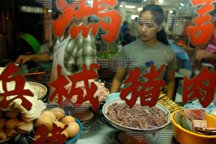 Server at a Chinese food stall (selling pork liver noodles) at a mostly Chinese night food market on Jalan Alor in the Golden Triangle.