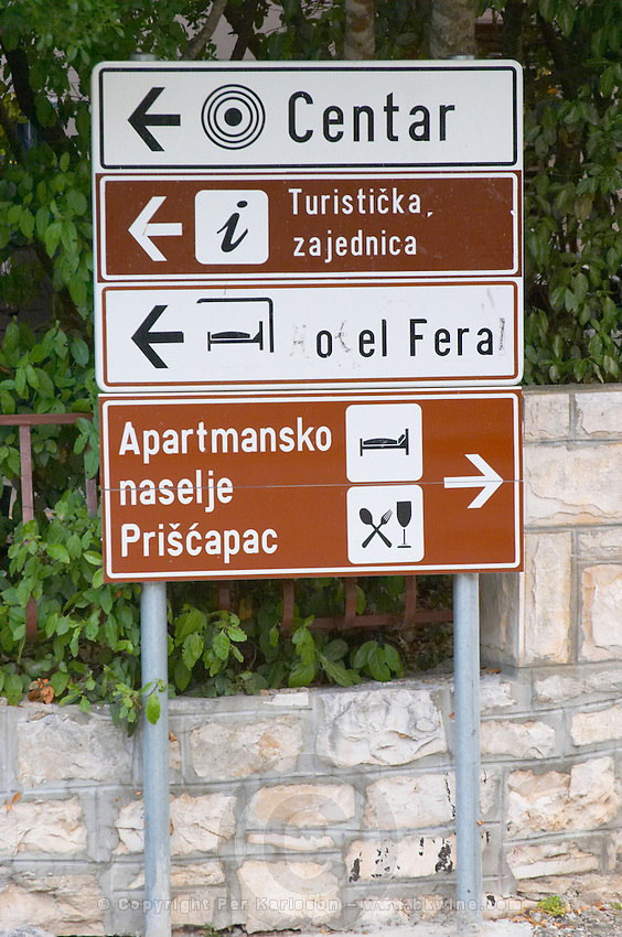 Road signs pointing with arrows to the town centre and to hotels and restaurants Korcula Island. Korcula Island. Dalmatian Coast, Croatia, Europe.