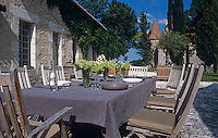 A table laid for lunch in front of the restored house with a view of the chateau beyond
