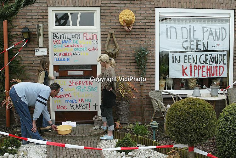 """Foto: VidiPhoto..ECHTELD - Ze plegen een economisch delict, maar desondanks niet van plan hun vijf gezonde kippen preventief te laten ruimen. Marga en Peter Veld uit Echteld en hun drie kinderen hebben hun huis aan de Voorstraat volgehangen met spandoeken tegen de ruimingsplannen van minister Veerman. Hun vijf kippen worden veilig opgeborgen in de badkamer. """"Alleen over mijn lijk komt de AID naar binnen"""", zegt Marga (r) strijdlustig."""