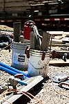 Job site close shot with buckets of trowels and bull floats after a concrete job