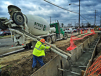 A worker guides concrete into a trench to cover newly laid underground utility conduit at State and Schrock in Westerville Ohio.
