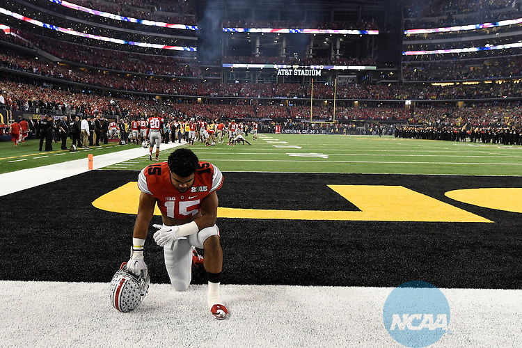 12 JAN 2015:  Ezekiel Elliott (15) of the Ohio State University prays before the College Football Playoff National Championship held at AT&T Stadium in Arlington, TX.  Ohio State defeated Oregon 42-20 for the national title.  Jamie Schwaberow/NCAA Photos
