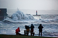 WEATHER PICTURE WALES<br /> Pictured: Onlookers watch as waves crash against the promenade wall and the lighthouse in the seaside town of Porthcawl, south Wales, UK. Wednesday 03 January 2018<br /> Re: Storm Eleanor affects parts of the UK.