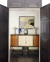The hallway is furnished with a French console and lamps and a painting by Rene Gruau