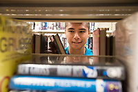 Jasper Khambaylarsirikul,'21, shelves books at the Redwood Library as he participates in the Salve Regina University Exploration Day of Service in Newport.