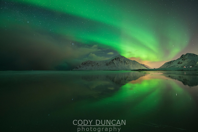 Northern Lights reflection on Skagsanden beach in winter, Flakstadøy, Lofoten Islands, Norway