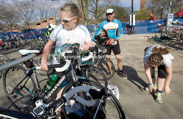 WATERBURY CT. 03 May 2014-050317SV07-Jill Rogoz of Prospect, left, gets her bike ready for the transition from running during The Greater Waterbury YMCA's Downtown Duathlon Race in Waterbury Saturday. Athletes ran a 5K race then transitioned to the bikes for a 14-mile ride. <br /> Steven Valenti Republican-American