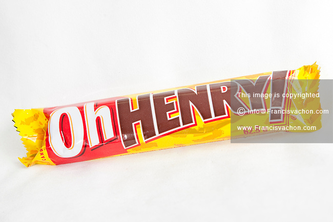 A Oh Henry chocolate bar over a white background. Nestle acquired the United States rights to the brand in 1984, where it continues to produce the bar; the bar is produced by The Hershey Company in Smith's Falls, Ontario, Canada.