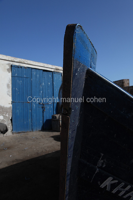 ESSAOUIRA, MOROCCO - MAY 10: A low angle view of the prow of a fishing boat on May 10, 2009 in Essaouira, Morocco. The traditional wooden boat is moored near the boathouse whose blue doors echo the blue of the sky in the morning sunshine. Essaouira, on the windswept Atlantic coast of Morocco, was re-built in the 18th century by French architect Theodore Cornut to the orders of Sultan Ben Abdullah. Surrounded by ramparts it is a charming small town now becoming more popular with tourists. (Photo by Manuel Cohen)