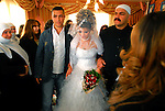 Arwad Abu Shaheen, center, is escorted by her brothers at the end of a farewell gathering at her house in Bukata, Golan Heights, as she sets off to marry her fiancé in Syria.