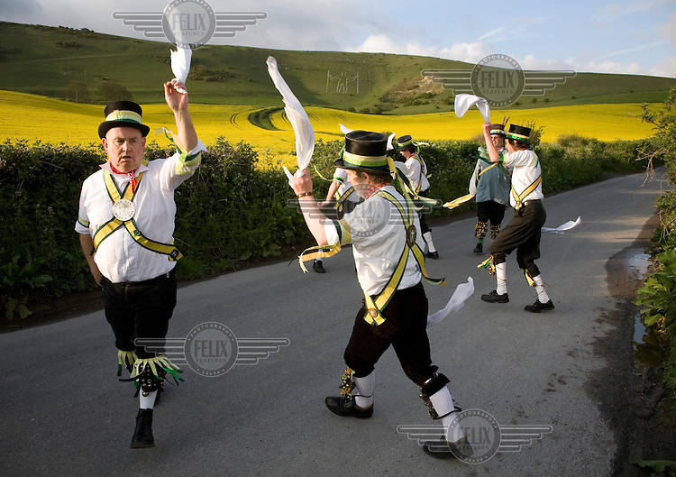 Members of The Longman Morris 'side' dance on mayday below the Longman of Wilmington in Sussex, which can be seen on the hillside. Morris dancing.