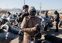 NWA Democrat-Gazette/CHARLIE KAIJO Terry Pollard of Gentry ties a face cover on Stacey Ann Wollman of Siloam Springs before a ride on Saturday, January 6, 2018 at Pig Trail Harley Davidson in Rogers. The Pig Trail Hog Chapter held their first meeting of the year with 65 members present out of 128 who re-signed. The members went on a group ride afterwards.