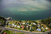 Aerial view of houses & wharf in the small settlement of Pukenui on the edge of the Houhora Harbour, Far North.Northland, New Zealand.