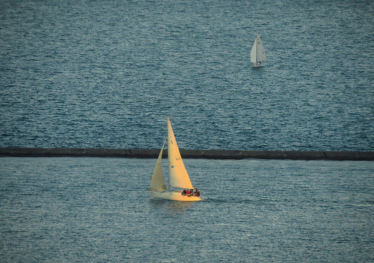 A sliver of late afternoon light illuminates a passing sailboat out on Lake Michigan and the sun drops towards the horizon. (DePaul University/Jamie Moncrief)