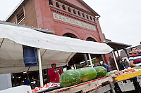 A woman selling watermelons is seen by a shed of the Detroit Eastern Farmers market in Detroit (Mi) Saturday June 8, 2013. The largest open-air flowerbed market in the United States, the Eastern Market is a historic commercial district in Detroit, Michigan.