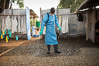 Tamba K. Kamano, hygienist, sprays a strong mixture of chlorine and water all around the ETU. Occidental College professor Mary Beth Heffernan works on her PPE Portrait Project with health care workers at the ELWA II ETU (Ebola treatment unit) in Monrovia, Liberia on Saturday, March 8, 2015.<br /> (Photo by Marc Campos, Occidental College Photographer) Mary Beth Heffernan, professor of art and art history at Occidental College, works in Monrovia the capital of Liberia, Africa in 2015. Professor Heffernan was there to work on her PPE (personal protective equipment) Portrait Project, which helps health care workers and patients fighting the Ebola virus disease in West Africa.<br />