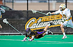 10 April 2011: University at Albany Great Dane defender Cody Futia, a Freshman from Schenectady, NY, is tripped up by University of Vermont Catamount Garrett Virtue, a Sophomore from Rye, NY, during game action at Moulton Winder Field in Burlington, Vermont. The Catamounts defeated the visiting Danes 11-6 in America East play. Mandatory Credit: Ed Wolfstein Photo
