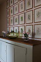 Arrangements of pink roses in glass vases and a green glass vase are displayed on a painted sideboard. A collection of botanical prints are arranged on the wall.
