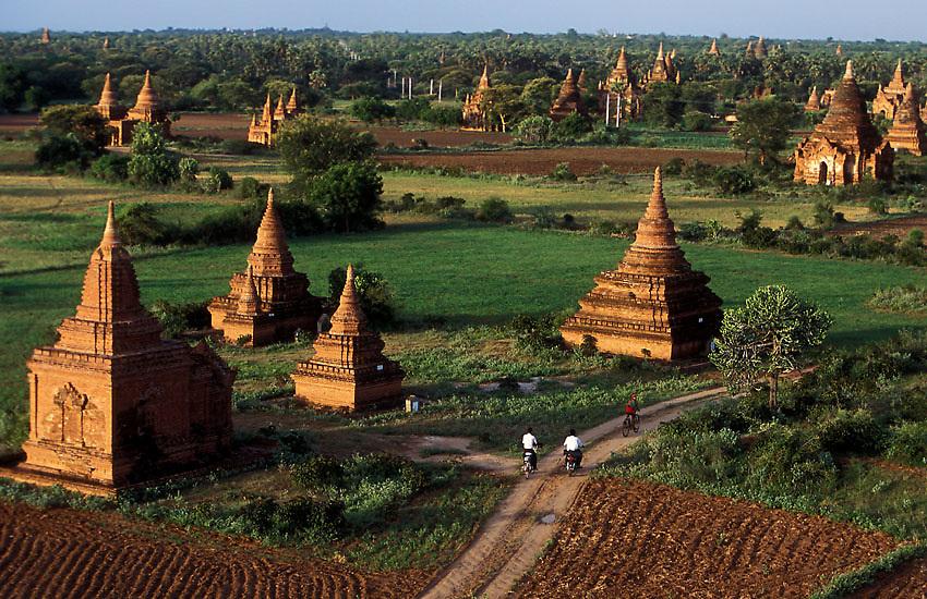 Three boys ride bikes through a field of Buddhist stupas at Bagan, Burma, July 2006. Photo: Ed Giles.