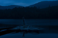 Boats at night blur during a long exposure on Shirakomaike Lake, Yatsugatake Range, Nagano, Japan.