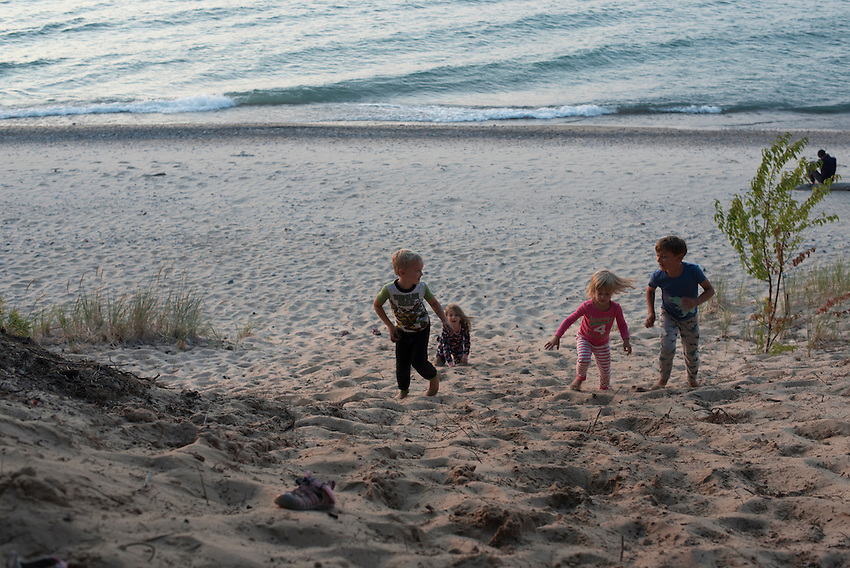 Children play on a sand dune in their pajamas while camping along Lake Superior in Michigan.