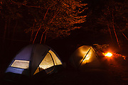 Tents in a White Mountain National Forest, New Hampshire campground during the night with camp fire in the background.
