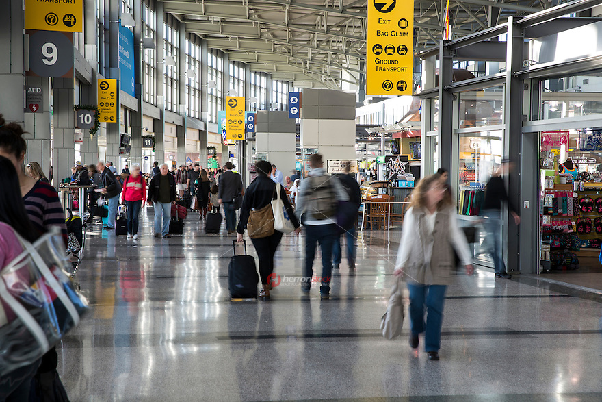 Passengers with luggage in hand walk through the Barbara Jordan Terminal at ABIA - Austin Bergstrom International Airport.