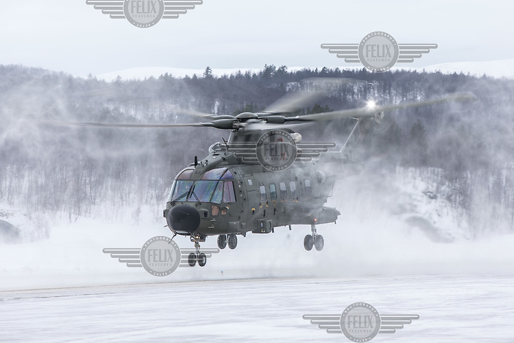 British Merlin helicopter perform a rolling take off, designed to avoid white out from the snow,  in the Arctic,  at Bardufoss, Norway. <br /> <br /> 845 Naval Air Squadron is a squadron of the Royal Navy's Fleet Air Arm. Part of the Commando Helicopter Force, it is a specialist amphibious unit operating the Leonardo Commando Merlin Mk3 helicopter and provides troop transport and load lifting support to 3 Commando Brigade Royal Marines.<br /> <br /> ©Fredrik Naumann/Felix Features